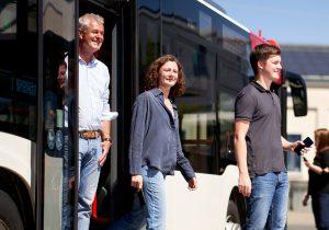Ein mann, eine Frau und ein Mann steigen mit den Handys in der Hand aus einem Bus aus.
